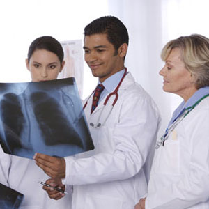 Medical professionals examining a patient's X-ray.