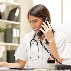A medical professional speaking with a patient over the phone.